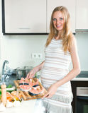 Schwangere Frau kocht Lachse Stockfotografie