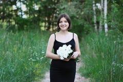 Schwangere Frau lächelt, hält weiße Blumen und untersucht die Kamera Stockfoto