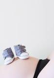 Schwangere Frau mit Babyschuhen Stockfotografie