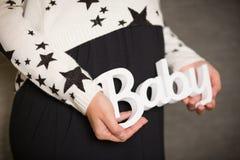 Schwangere Frau mit Babyzeichen Horizontale Nahaufnahme eines schwangeren Bauches mit Zeichenbaby stockfotos