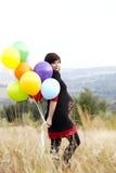 Schwangere Frau mit Ballonen im Gras Stockfotos