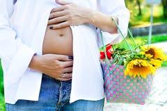 Schwangere Frau mit Blumen lizenzfreie stockfotografie