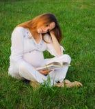 Schwangere Frau mit Buch Stockfoto