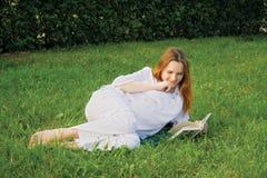 Schwangere Frau mit Buch Stockfotografie