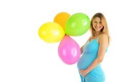 Schwangere Frau mit bunten Ballonen Stockbild