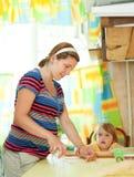 Schwangere Frau mit dem Kind, das Mehlklöße bildet Stockfotografie
