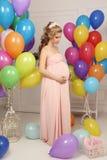 Schwangere Frau mit dem langen blonden Haar im eleganten Kleid, mit vielen bunten Luftballonen Lizenzfreie Stockfotos