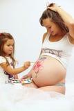 Schwangere Frau mit dem netten Tochterlackbauch Stockbild