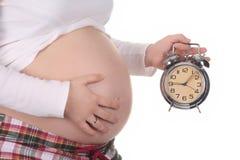 Schwangere Frau mit der Alarmuhraufwartung Stockbilder
