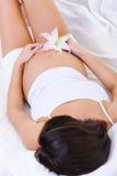 Schwangere Frau mit der Blume auf ihrem Bauch Stockbilder