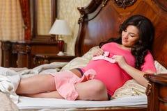 Schwangere Frau mit der Kleidung der Kinder. Stockfoto
