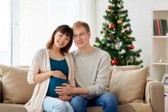 Schwangere Frau mit Ehemann zu Hause am Weihnachten Stockfoto