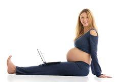Schwangere Frau mit einem Laptop, der auf dem Fußboden sitzt Lizenzfreies Stockbild