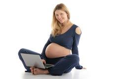 Schwangere Frau mit einem Laptop, der auf dem Fußboden sitzt Lizenzfreie Stockfotos