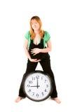 Schwangere Frau mit einer Borduhr stockfotos