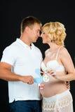 Schwangere Frau mit ihrem Ehemann, der einen Spielzeugstorch auf dem Hintergrund des Bauches auf einem schwarzen Hintergrund hält Stockbilder