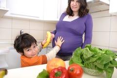 Schwangere Frau mit ihrem Sohn in der Küche Lizenzfreie Stockbilder