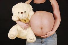 Schwangere Frau mit kleinem Bären Lizenzfreies Stockfoto