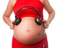 Schwangere Frau mit Kopfhörern nah an ihrem Bauch Stockbild