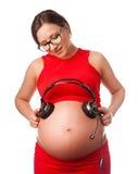 Schwangere Frau mit Kopfhörern nah an ihrem Bauch Stockfotos