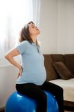 Schwangere Frau mit Rückenschmerzen Stockfoto