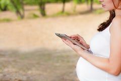 Schwangere Frau mit Tablet-PC Stockfotos