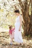 Schwangere Frau mit Tochter im Park Lizenzfreies Stockfoto