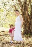 Schwangere Frau mit Tochter im Park Lizenzfreie Stockfotografie