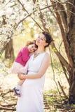 Schwangere Frau mit Tochter im Park Lizenzfreies Stockbild