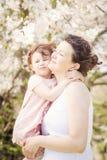 Schwangere Frau mit Tochter im Park, der das Küssen umarmt Lizenzfreie Stockfotos