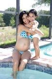 Schwangere Frau Poolside mit Kleinkind-Tochter (3) Stockfotografie