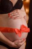 Schwangere Frau, rotes Band um Magen Stockfoto