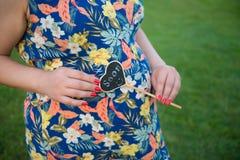 Schwangere Frau, Schwangerschaft, Vater und Mutter, neues WarteBaby, neugeborenes Baby, Schuhe des neugeborenen Babys stockbild