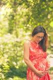 Schwangere Frau am sonnigen Tag des Sommers Stockfotos