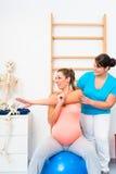 Schwangere Frau tut das Ausdehnen von Übungen mit körperlichem Therapeuten stockbild