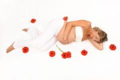 Schwangere Frau umgeben durch Blumen Stockfoto