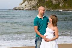 Schwangere Frau und ihr Ehemann, die durch das Meer schlendert. Lizenzfreies Stockbild