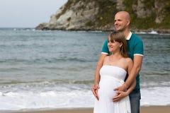 Schwangere Frau und ihr Ehemann, die durch das Meer schlendert. Stockfotografie
