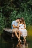 Schwangere Frau und ihr Ehemann, die an einem See sitzt, während er ihre Schulter leicht küsst lizenzfreies stockfoto