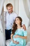 Schwangere Frau und ihr Ehemann im Studio Stockbild