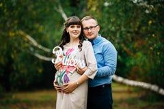 Schwangere Frau und ihr reizendes Umarmen des hübschen Ehemanns auf Natur, haben Picknick im Park Stockbild