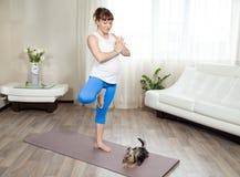 Schwangere Frau und ihr Schoßhund, die zu Hause Yoga tut Stockfotos