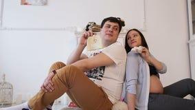 Schwangere Frau und ihre Ehemann- und neugeborenekleidung stock footage