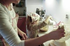 Schwangere Frau und kleines Mädchen, die in der Küche kocht lizenzfreie stockfotografie