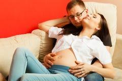 Schwangere Frau und Mann, die auf Sofa sich entspannt Lizenzfreie Stockfotografie