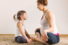 Schwangere Frau und wenig Tochteryogatrainieren Lizenzfreies Stockfoto