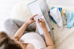 Schwangere Frau wird zur Geburtsklinik fertig und verpackt Babymaterial Schwangerschaft, Geburtskonzept lizenzfreie stockbilder