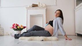 Schwangere Frauen-Holding-Babyschuhe auf ihrem Bauch stock footage
