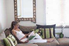Schwangere Frauen-Lesebuch auf Sofa Stockbild
