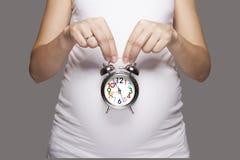 Schwangere Frauen mit Wecker Stockfotografie